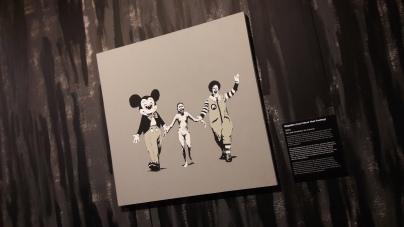 Napalm, Can't Beat That Feeling, Banksy (2004) Détournement du cliché pris par le photographe vietnamien le 8 juin 1972 à Trang Bang, montrant une jeune enfant (Kim Phuc) brûlée au napalm.